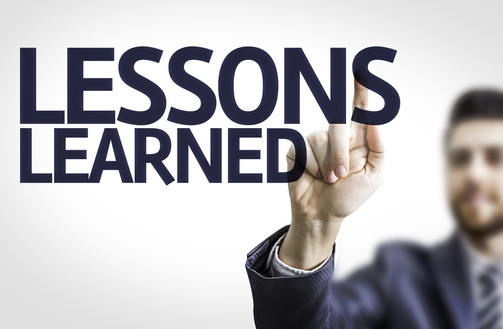 Business man pointing to transparent board with text Lessons Learned